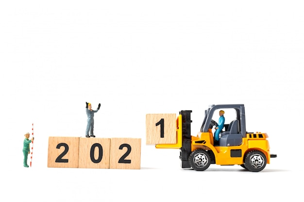 ミニチュアワーカーチームが木製のブロック番号2021を作成