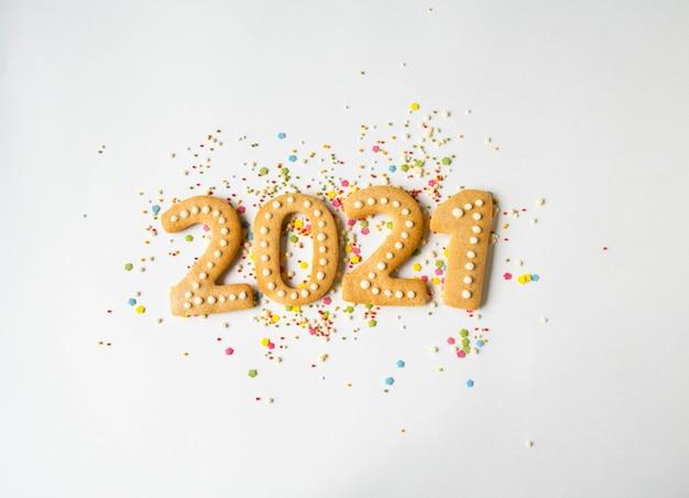Разноцветная выпечка сахарного топинга и пряник в виде цифр 2021 на белом фоне