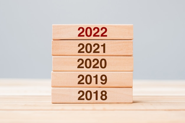 2022 block over 2021, 2020 and 2019 wooden building on table background. business planning, risk management, resolution, strategy, solution, goal, new year and happy holiday concepts