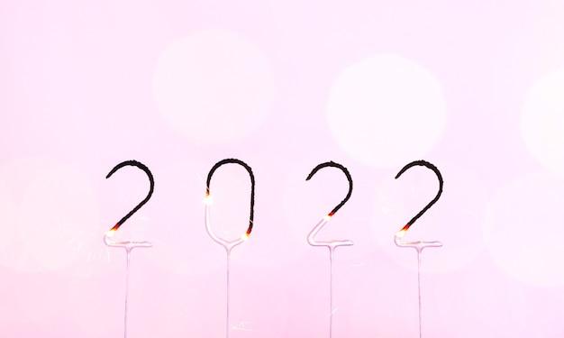 2022年に燃える線香花火の番号がピンクの背景にぼやけたボケ光の明けましておめでとうとメリーc ..