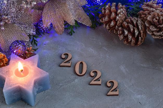 Новогодняя композиция 2022 года в серебристо-синем цвете, синяя гирлянда, свеча и еловые ветки