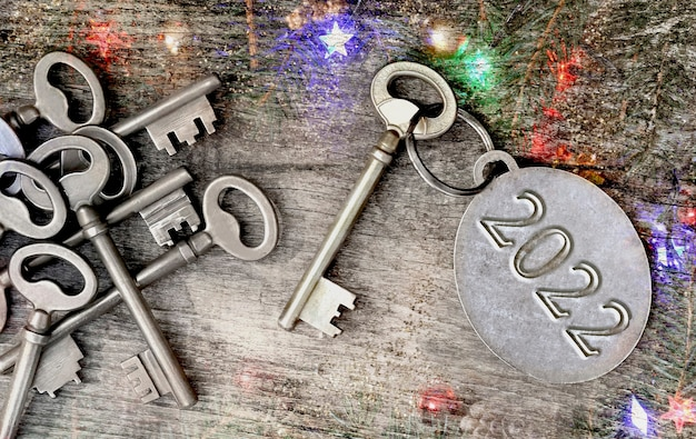 2022 engraved on a ring of an old key in christmas  lights ornament  background