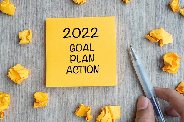 2022 goal, plan, action word on yellow note with businessman holding pen and crumbled paper on wooden table background. new year new start, resolutions, strategy  concept