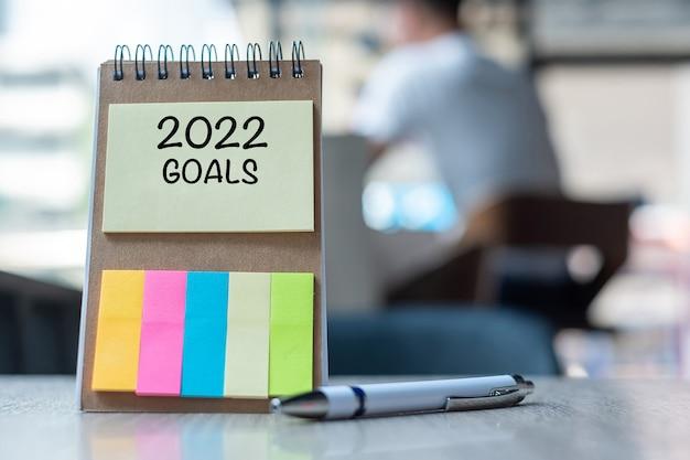 2022木製のテーブルにペンでメモ用紙に目標の言葉。解決策、戦略、ソリューション、目標、ビジネス、新年の新しいあなたと幸せな休日の概念