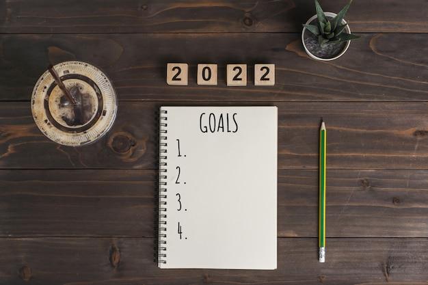 Текст цели 2022 на блокноте с чашкой кофе и ручкой на деревянном столе