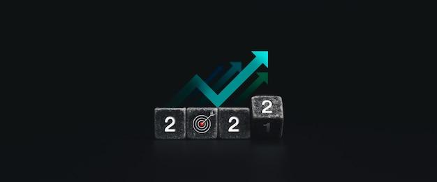 2022年明けましておめでとうございます。目標ターゲットアイコンシンボルと暗い背景、最小限のスタイルの蜂起矢印で黒いサイコロブロックを反転する白い2022年の数字で成功したコンセプトバナー。
