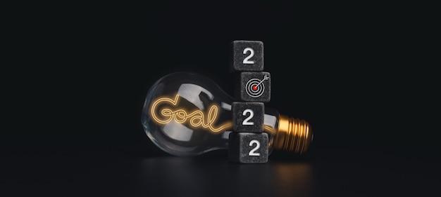 目標と成功のコンセプトを持つ2022年明けましておめでとうバナー。黒のダイススタッキング、ターゲットアイコン、暗い背景にネオンライトスタイルの単語が付いた電球、モダンでミニマルなスタイルの2022年の数字。