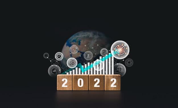 2022年明けましておめでとうございますバナーと目標目標と成功したコンセプト。現代の成長チャート、ビジネス戦略アイコン、暗い背景の地球と木製の立方体ブロックの2022年の数字。