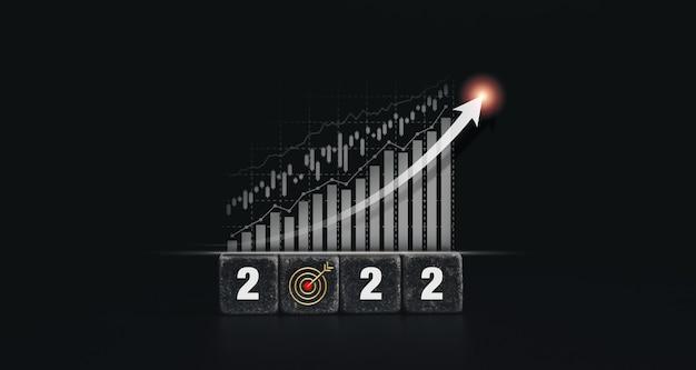 2022年明けましておめでとうございますバナーと目標目標と成功したコンセプト。暗い背景、モダンで最小限のスタイルの木製の立方体ブロックの2022年の数字の成長と成功のビジネスファイナンスチャートグラフ。