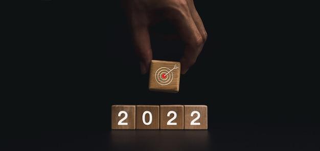 2022年明けましておめでとうございますビジネス目標のコンセプト。暗い背景、モダンでミニマルなスタイルの2022年の数字のブロックに目標ターゲットアイコンのシンボルが付いた大きな木製のブロックを手で置きます。