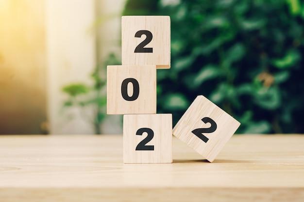 햇빛 나무 테이블에 나무 블록에 2022 해피 뉴가 어. 새 해 개념입니다.
