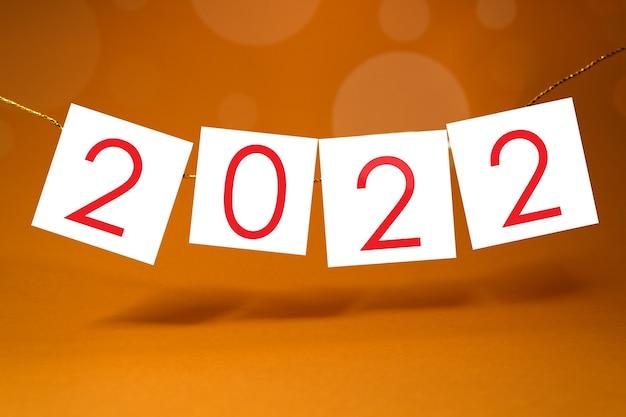 黄色のornage背景の挨拶とカレンダーのための2022年明けましておめでとうございますテンプレート