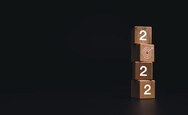 2022年明けましておめでとうございます。 2022年の数字と赤いターゲットアイコンのシンボルがコピースペース、モダンで最小限のスタイルで暗い背景に木製の立方体ブロックのスタックでビジネス目標の概念。