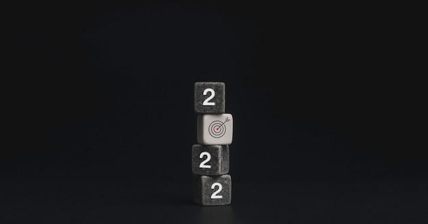 2022 с новым годом. бизнес-цель с целевым значком подписывается на стопке черных каменных кубических блоков на темном фоне. добро пожаловать, счастливого рождества и счастливого нового года на баннере 2022 года.