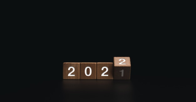 2022 happy new year welcome and merry christmas banner. flipping wooden cube blocks for changing the year from 2021 to 2022 on dark background.