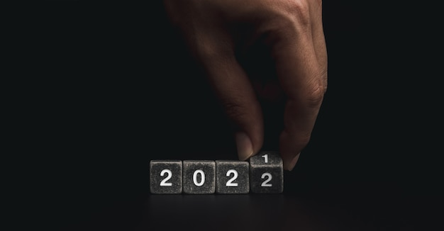 2022 happy new year welcome and merry christmas banner. hand flipping black stone cube blocks for changing the year 2021 to 2022 on dark background.