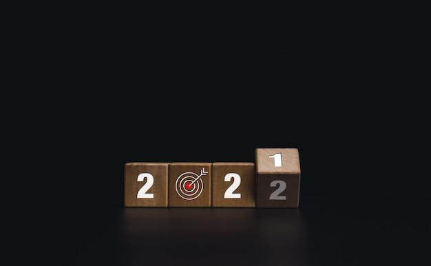 2022年明けましておめでとうございます。ビジネス目標と成功のコンセプトがあります。コピースペース、モダンでミニマルなスタイルの暗い背景で、2021年から2022年までの番号を変更するための木製の立方体ブロックの反転。