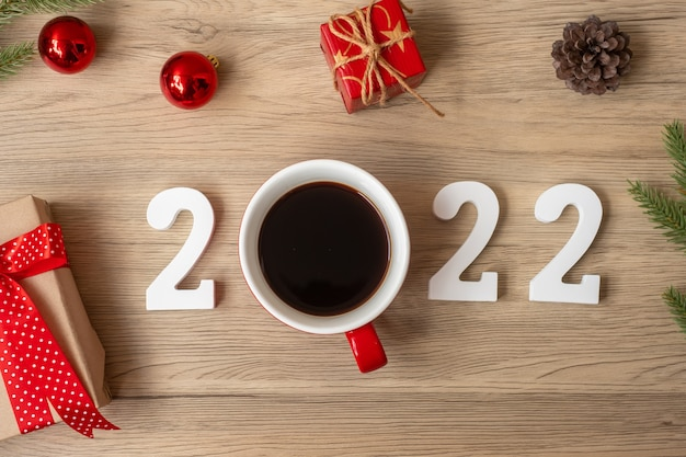 2022 happy new year with coffee cup and christmas decoration on wood table background. new start, resolution, countdown, goals, plan, action and mission concept