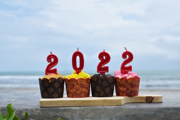 2022 happy new year with cupcakes and candles on the beach