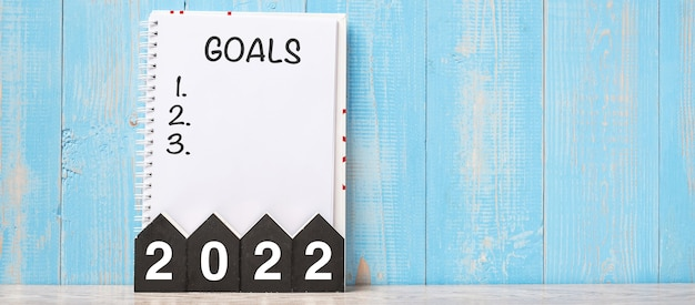 2022 happy new year with goal word and wooden number. time for a new start, resolution, plan, action and mission concept