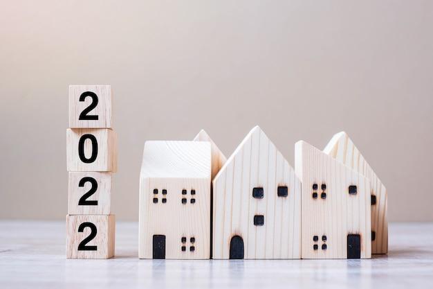2022년 새해 복 많이 받으세요 테이블 나무 배경에 집 모델이 있습니다. 은행, 부동산, 투자, 금융, 저축 및 새해 해상도 개념