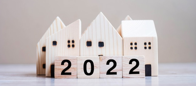 2022 happy new year with house model on table wooden background. banking, real estate, investment, financial, savings and new year resolution concepts