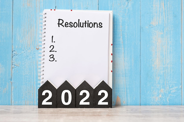 2022 happy new year with resolutions word and wooden number. time for a new start, goal, plan, action and mission concept