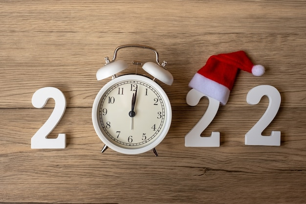 2022 happy new year  with retro alarm clock and wooden number. merry christmas, new start, resolution, countdown, goals, plan, action and mission concept