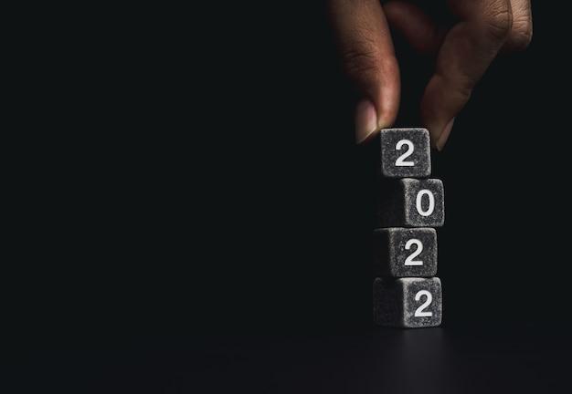 2022年明けましておめでとうございます。ビジネス目標をコンセプトにしています。コピースペース、モダンで最小限のスタイルで暗い背景にサイコロブロックの2022年の数字のスタックの上に黒いサイコロを置く手。
