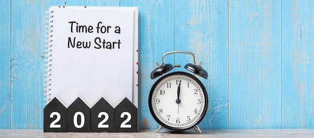 2022年明けましておめでとうございます。新しいスタートの時間、黒いレトロな目覚まし時計、木製の数字。解決策、目標、計画、行動、ミッションのコンセプト