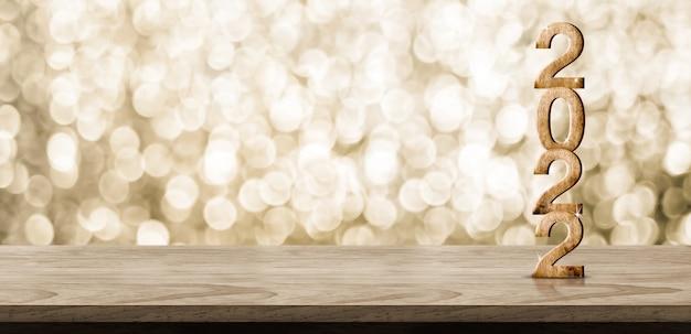 きらめく金のボケ壁が付いている木のテーブルの2022年の新年あけましておめでとうございます木の番号(3dレンダリング)、クリスマスと新年の休日のプロモーションのための製品の展示のためのスペースを残してください