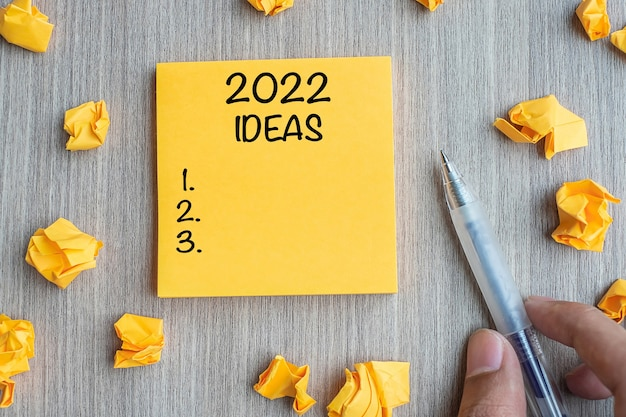 2022 idea word on yellow note with businessman holding pen and crumbled paper on wooden table background. new year new start, resolutions, strategy, mission concept