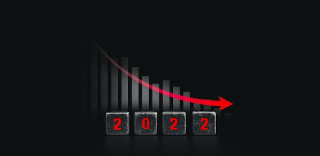2022年の新年と経済危機のコンセプトバナー。黒いサイコロブロックに赤い2022年の数字が表示され、暗い背景、モダンで最小限のスタイルのビジネスチャートグラフに赤い下向き矢印が表示されます。