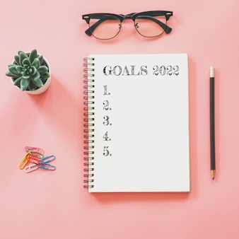 2022 new year concept. goals list in notepad, smartphone, stationery on pink pastel color with copy space