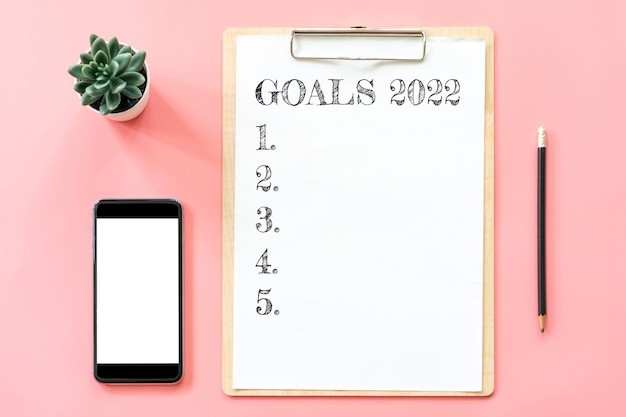 2022 new year concept. goals list in stationery, blank clipboard, smartphone, pot plant on pink pastel color with copy space