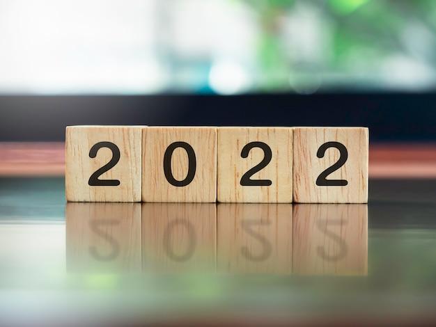 2022年、新年のコンセプト、茶色の木製の机と緑の自然の背景に木製の立方体のブロックの数字。