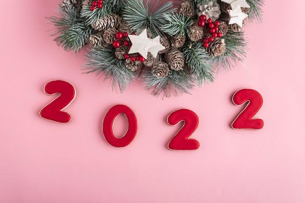 ピンクの背景にジンジャーブレッドとクリスマスリースから2022年の新年。明けましておめでとうございます2022。