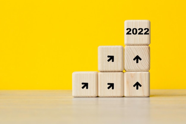 2022년 새해. 관심 증가 추세. 노란색 배경에 큐브입니다. 성장을 상징합니다. 비즈니스 개념입니다. 복사 공간입니다.