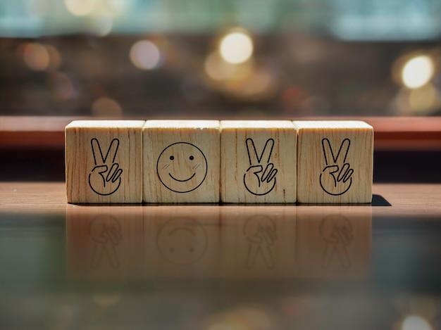 2022年、新年は前向きなコンセプト、2本の指、茶色の木製デスクの木製キューブブロックの年番号としての笑顔のアイコンで始まり、照明ボケの背景を祝います。