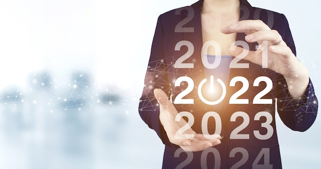 2022 new year. two hand holding virtual holographic 2022 icon with light blurred background. happy new year 2022. success new year concept.business management,inspiration concepts ideas.