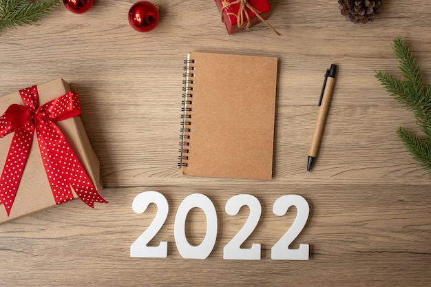2022年の新年、ノート、クリスマスプレゼント、木製のテーブルにペン。クリスマス、明けましておめでとう、目標、決議、やることリスト、開始、戦略と計画の概念