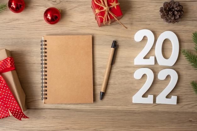 2022년 새해에는 노트북, 크리스마스 선물, 펜이 나무 테이블에 있습니다. 크리스마스, 새해 복 많이 받으세요, 목표, 해결, 할 일 목록, 시작, 전략 및 계획 개념