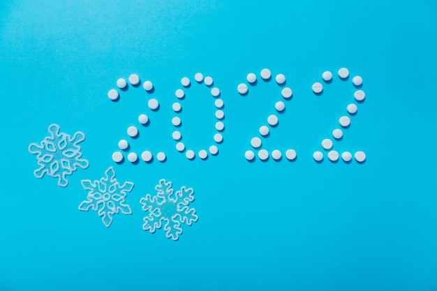 2022 new year written with white pills and snowflakes the concept of medical treatment