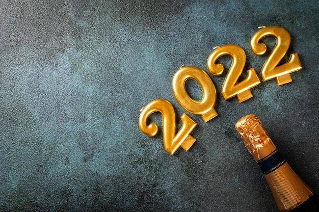 シャンパンボトルと装飾が施された2022年の数字。明けましておめでとうとお祝いのコンセプト。上部の水平ビューのコピースペース。明けましておめでとうございます。クリスマスフラットレイ。新年2022年。新年のコンセプト。