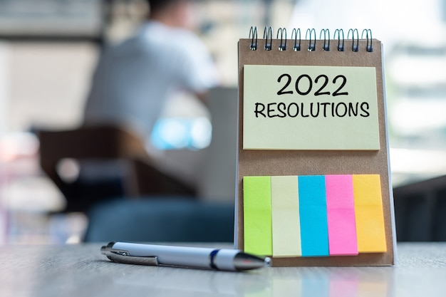 2022 resolution word on note paper with pen on wooden table. strategy, solution, goal, business, new year new you and happy holiday concepts