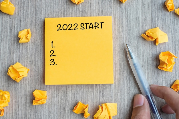 2022 start word on yellow note with businessman holding pen and crumbled paper on wooden table background. new year, resolutions, strategy and goal concept