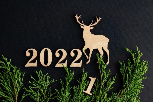 2022 стильная новогодняя композиция на черном фоне деревянный олень еловые ветки копией пространства