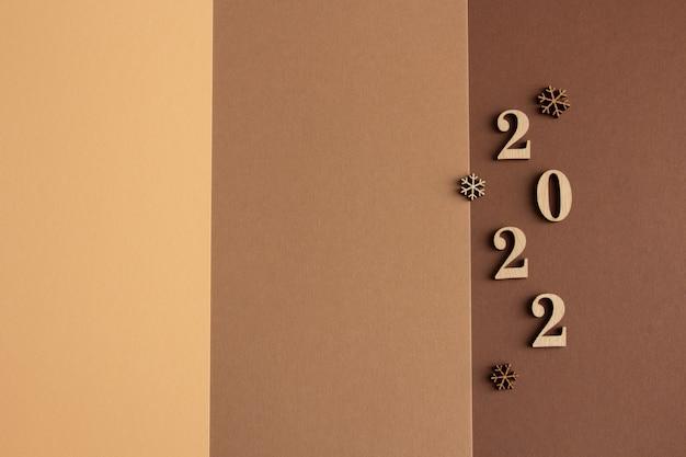 2022 стильная новогодняя композиция на коричнево-бежевом фоне деревянные фигурки копируют пространство