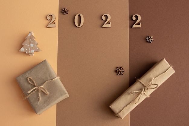 2022 стильная новогодняя композиция на коричневом фоне. подарки и деревянные фигурки копируют пространство.
