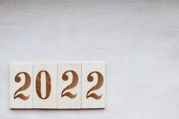2022 год - новогодний номер выложен деревянными цифрами на деревянной поверхности с новым годом.